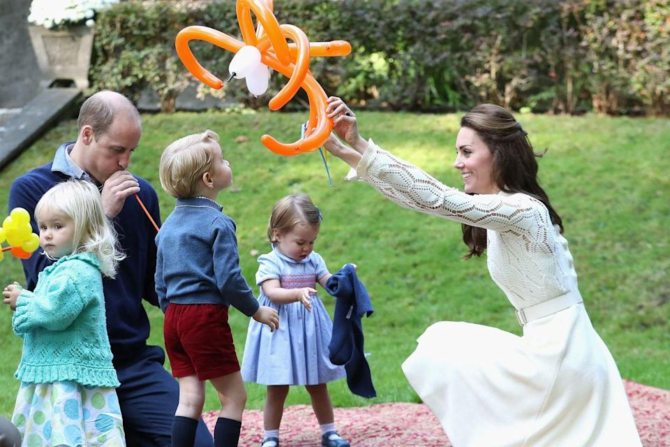 "<p>The Duchess plays with balloon animals on the grass with Prince William, Prince George, and Princess Charlotte while at a party for military families during a royal tour of <a href=""https://www.harpersbazaar.com/fashion/street-style/g7897/kate-middleton-royal-canada-tour-fashion/"" rel=""nofollow noopener"" target=""_blank"" data-ylk=""slk:Canada"" class=""link rapid-noclick-resp"">Canada</a>.</p>"