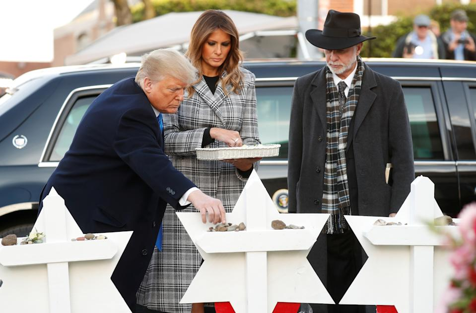 President Trump places a stone as he stands with first lady Melania Trump and Rabbi Jeffrey Myers at a makeshift memorial for the victims of the Tree of Life Synagogue massacre in Pittsburgh, Oct. 30, 2018. (Kevin Lamarque/Reuters)