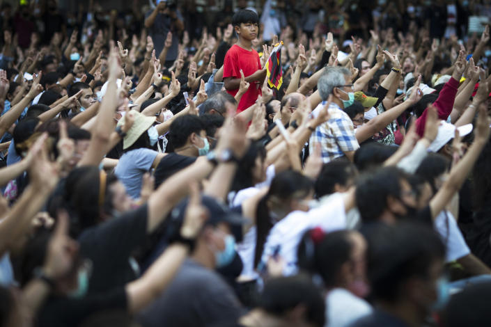 Pro-democracy protesters flash the three-finger protest salute during an anti-government rally at a major intersection in Bangkok, Thailand, Wednesday, Nov. 18, 2020. Police in Thailand's capital braced for possible trouble Wednesday, a day after a protest outside Parliament by pro-democracy demonstrators was marred by violence that left dozens of people injured. (AP Photo/Wason Wanichakorn)