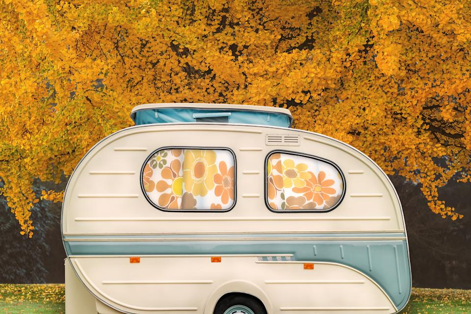 Vintage seventies white caravan with flower curtains in front of an autumn tree