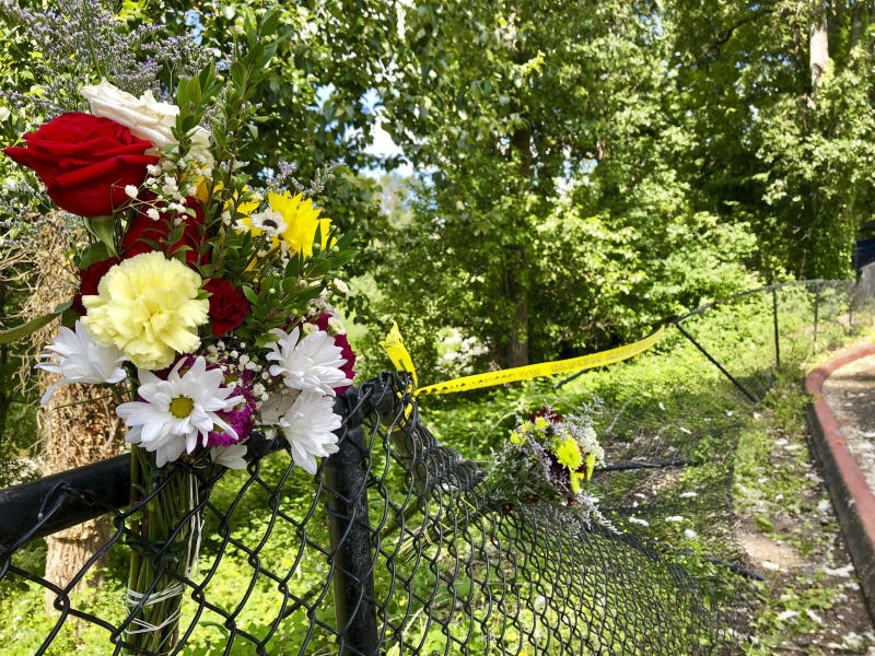 Bouquets of flowers sit on a fence on Wednesday, June 26, 2019, that was knocked down when a driver crashed into a swimming hole in Washougal, Wash., and ran over two German tourists who were sunbathing by the Washougal River, killing them. Police have arrested David Croswell, who lives a few blocks away from the swimming hole, in the deaths of Rudolf Hohstadt, 61, and Regina Hohstadt, 62. (AP Photo/Gillian Flaccus)