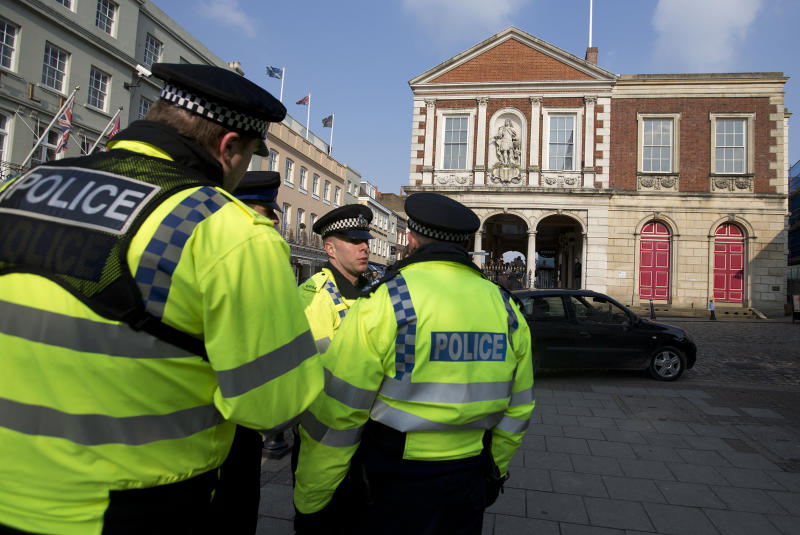 Officers of the Thames Valley police wait outside the Guildhall in Windsor, England as the inquest into the death of Russian oligarch Boris Berezovsky takes place, Thursday, March, 28, 2013. Berezovsky was found dead at his home in Ascot near Windsor on Saturday March 23.(AP Photo/Alastair Grant)