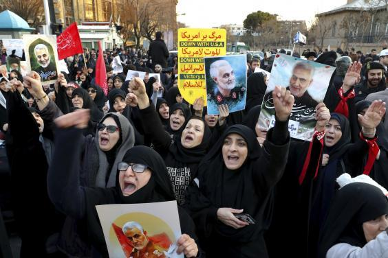 Chanting protesters outside the British embassy in Tehran hold up pictures of the general (AP)