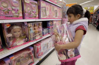 FILE - In this Jan. 29, 2007, file photo Yvette Ibarra holds a Dancing Princess Barbie doll while shopping at a toy store in Monrovia, Calif. Gov. Gavin Newsom signed 92% of the new laws lawmakers sent him at the end of this years legislative session that ended Sept. 10. One of the bills he approved makes California the first state to require large department stores to display products like toys and toothbrushes in gender-neutral ways. It does not outlaw traditional boys and girls sections at department stores, but says large stores must also have a gender-neutral section. (AP Photo/Nick Ut, File)
