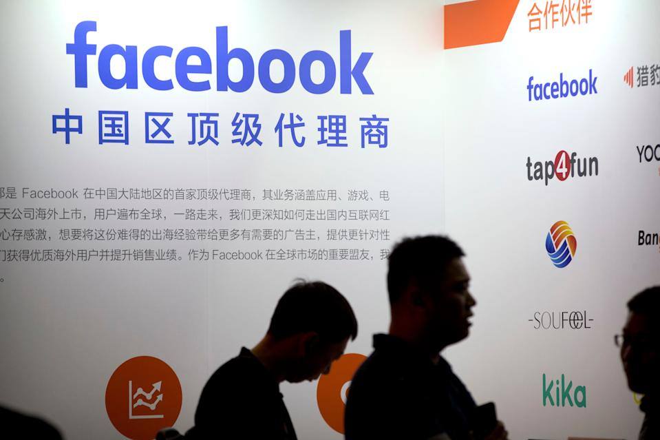 """Visitors walk past the Facebook logo at an exhibitor's display at the Global Mobile Internet Conference (GMIC) in Beijing, Thursday, April 26, 2018. The GMIC features current and future trends in the mobile Internet industry by some major foreign and Chinese internet companies. The text reads """"first-rate commercial agent for China"""". (AP Photo/Mark Schiefelbein)"""