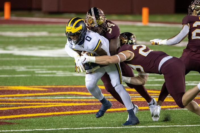Michigan receiver Giles Jackson is tackled by Minnesota defensive lineman Boye Mafe (34) and defensive back Matt Guggemos (28) in the first quarter at TCF Bank Stadium, Oct. 24, 2020.