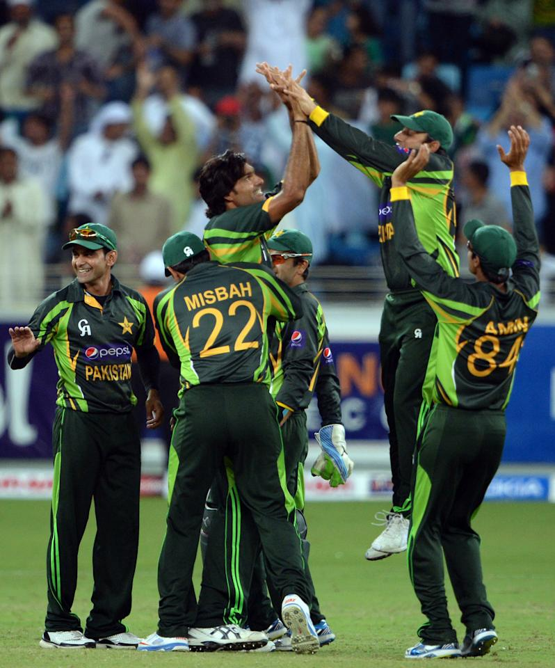 Pakistani bowler Mohammad Irfan (C) celebrates with team-mates after taking a wicket from South African batsman JP Duminy (unseen) during the second day-night international against South Africa in Dubai Cricket Stadium in Dubai on November 1, 2013. Pakistan were bowled out for 209 in their innings. South Africa lead the five-match series 1-0. AFP PHOTO/ Asif HASSAN        (Photo credit should read ASIF HASSAN/AFP/Getty Images)
