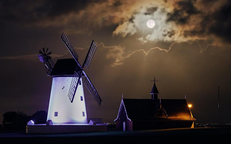 October Harvest Moon: The full harvest moon rises over the White Windmill in Lytham St Annes - www.alamy.com