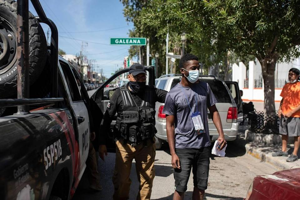 A migrant from Haiti is detained by Mexican immigration officers in Ciudad Acuña, Mexico, Wednesday, Sept. 22, 2021, near the U.S. border in Texas.