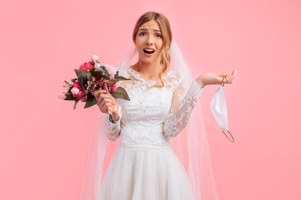 Beautiful bride in a wedding dress with a medical protective mask in her hands, on a pink background. Quarantine, wedding, coronavirus