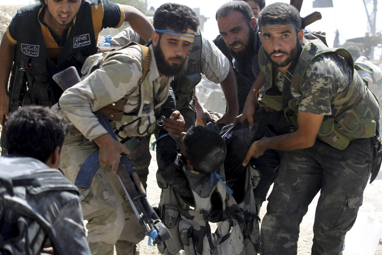Free Syrian Army fighters carry their fellow fighter after he was wounded on the front line in Aleppo's Sheikh Saeed neighbourhood September 21, 2013. REUTERS/Molhem Barakat (SYRIA - Tags: CIVIL UNREST POLITICS TPX IMAGES OF THE DAY CONFLICT)