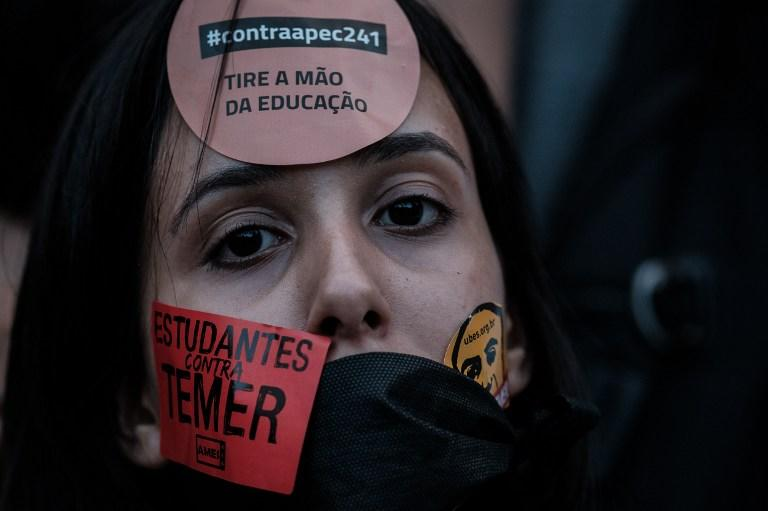 <p>A woman takes part in a protest against President Michel Temer's government constitutional amendment (PEC) 241, in Rio de Janeiro, Brazil, on October 17, 2016. Approved by Brazil's lower house, the constitutional amendment limits budget increases to the rate of inflation for the next 20 years. Leftist lawmakers had fought against the spending cap, arguing that it would dramatically worsen conditions for ordinary Brazilians, especially the poor. / AFP PHOTO / YASUYOSHI CHIBA </p>