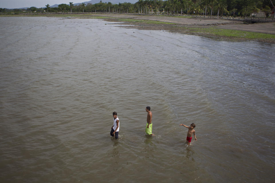 Youths wade through Cocibolca Lake, also known as Nicaragua Lake, in Granada, Nicaragua, Friday, June 7, 2013. A concession to build a canal across Nicaragua linking the Pacific Ocean and Caribbean Sea, which would go through the waters of Lake Nicaragua, will be awarded to a Chinese company, the National Assembly president said Wednesday. (AP Photo/Esteban Felix)