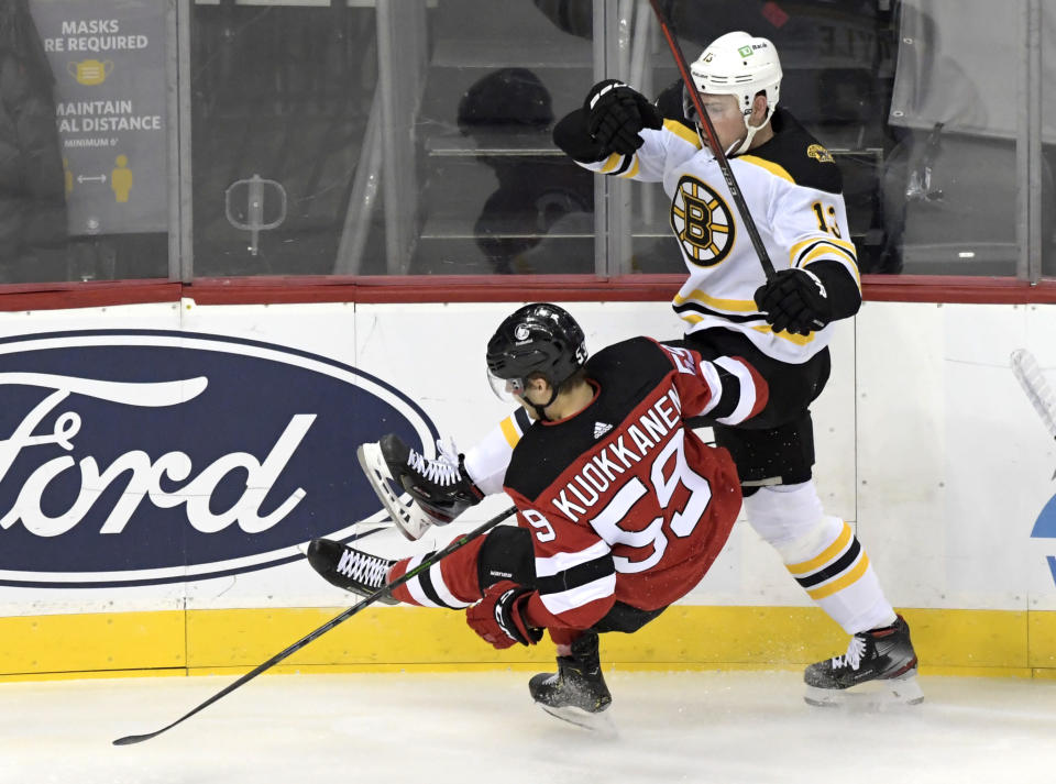 Boston Bruins center Charlie Coyle (13) checks New Jersey Devils center Janne Kuokkanen (59) to the ice during the first period of an NHL hockey game Saturday, Jan. 16, 2021, in Newark, N.J. (AP Photo/Bill Kostroun)