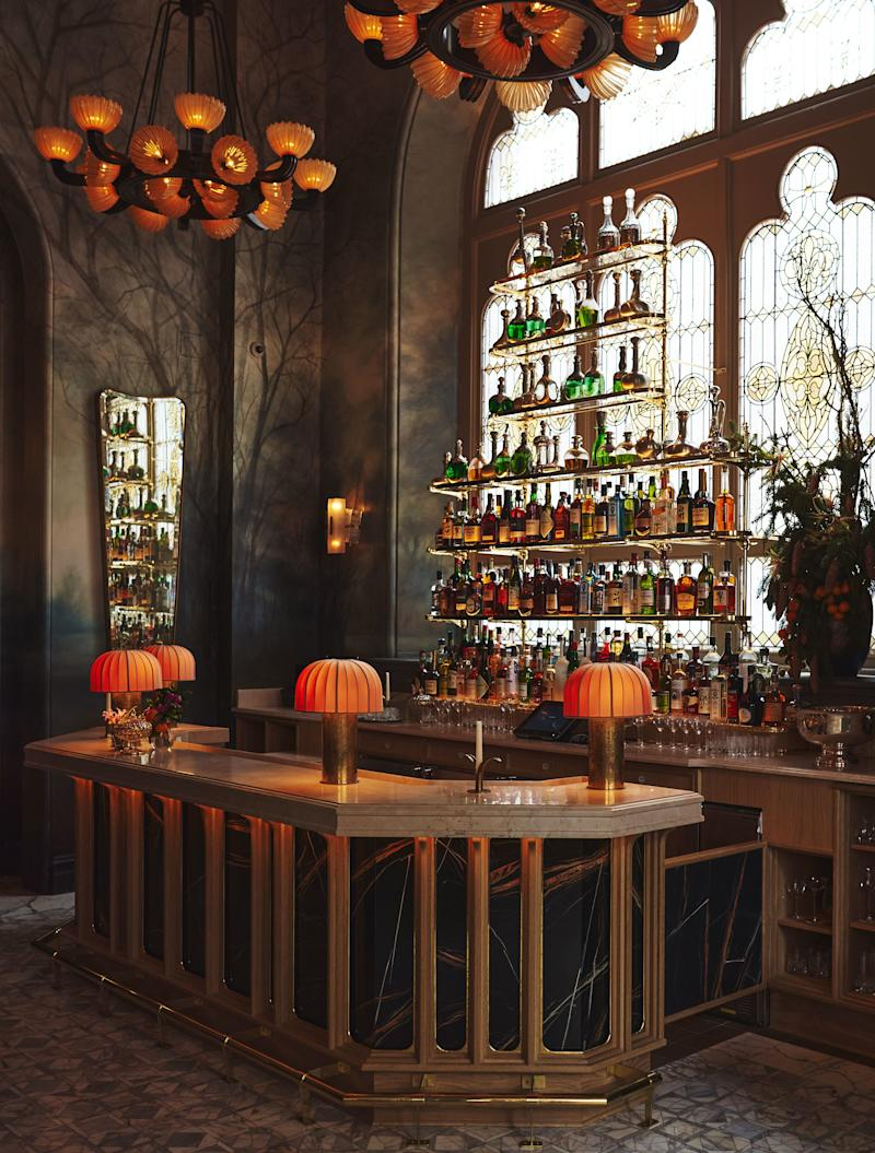 A Black St. Laurent marble bar and stained glass window alongside custom lighting adds intrigue to the cocktail area.