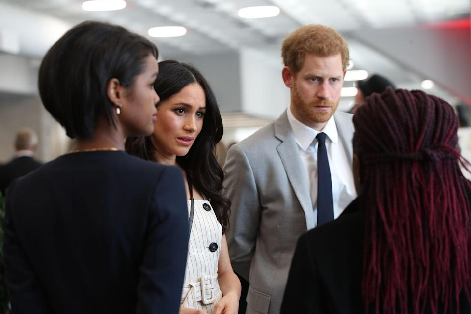 Prince Harry and Meghan talk with delegates during a reception for the Commonwealth Youth Forum in April (PA)