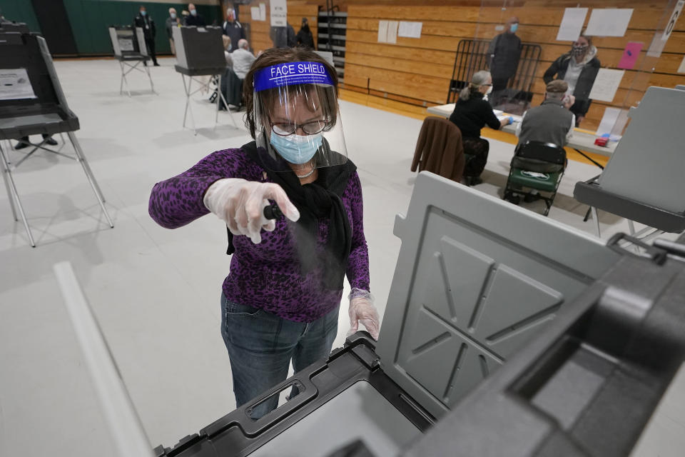 Poll worker Kathy Richardson uses a spray bottle to sanitize a voting booth out of concern for the coronavirus in a polling station at Marshfield High School, Tuesday, Nov. 3, 2020, in Marshfield, Mass. (AP Photo/Steven Senne)