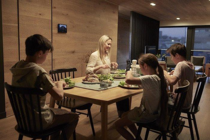 A family enjoys a home-cooked dinner surrounded by clean air and abundant natural light.