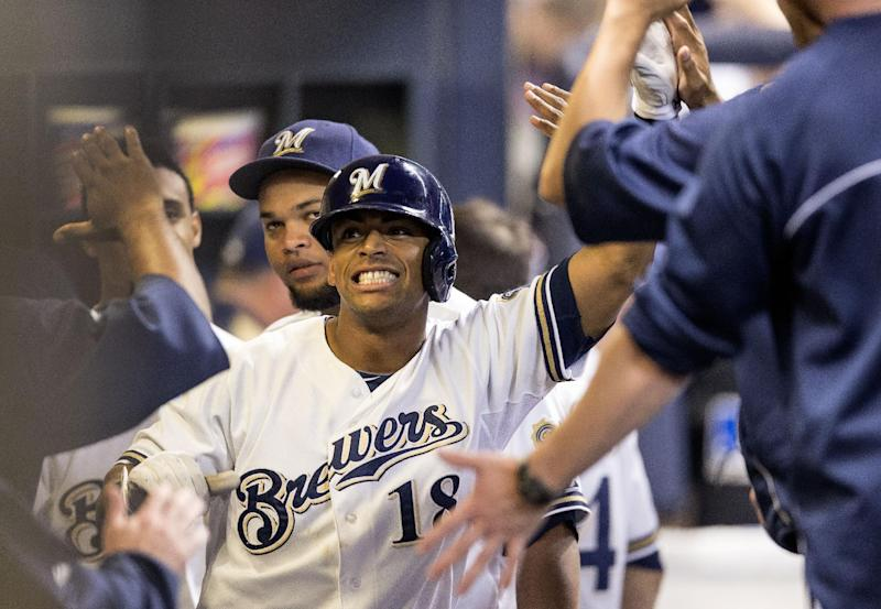Milwaukee Brewers' Khris Davis smiles while being greeted by teammates after hitting a solo home run during the fourth inning of a baseball game against the Chicago Cubs, Wednesday, Sept. 18, 2013, in Milwaukee. (AP Photo/Tom Lynn)