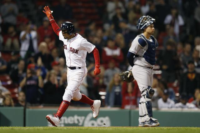 Boston Red Sox's Mookie Betts, left, celebrates his solo home run behind New York Yankees' Gary Sanchez during the eighth inning of a baseball game in Boston, Sunday, Sept. 8, 2019. (AP Photo/Michael Dwyer)