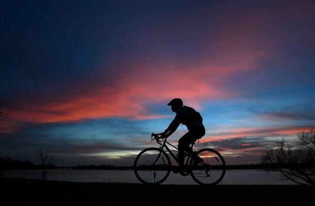 A cyclist is silhouetted on a path along the Ontario side of the Ottawa River on March 30, 2021. Outdoor exercise has been considered more safe in the pandemic as long as people keep their distance from each other. (Adrian Wyld/Canadian Press - image credit)