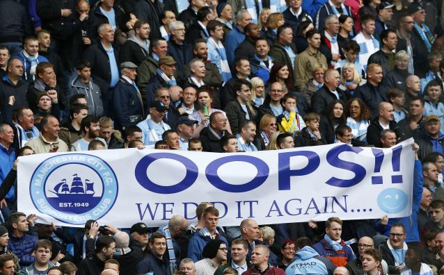 """Manchester City fans hold a banner as their team take on West Ham United during their English Premier League soccer match at the Etihad Stadium in Manchester, northern England May 11, 2014. REUTERS/Darren Staples (BRITAIN - Tags: SPORT SOCCER) FOR EDITORIAL USE ONLY. NOT FOR SALE FOR MARKETING OR ADVERTISING CAMPAIGNS. NO USE WITH UNAUTHORIZED AUDIO, VIDEO, DATA, FIXTURE LISTS, CLUB/LEAGUE LOGOS OR """"LIVE"""" SERVICES. ONLINE IN-MATCH USE LIMITED TO 45 IMAGES, NO VIDEO EMULATION. NO USE IN BETTING, GAMES OR SINGLE CLUB/LEAGUE/PLAYER PUBLICATIONS"""