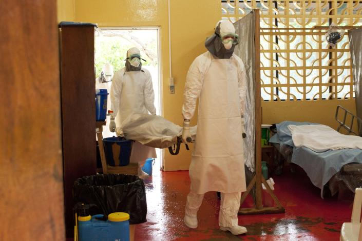 Dr. Kent Brantly (R) carrying in an Ebola patient before he became contaminated with the disease himself. (Courtesy Samaritan's Purse)