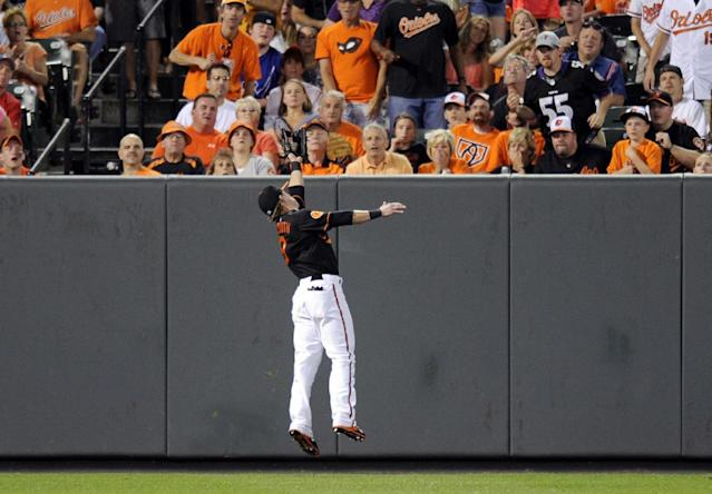 Baltimore Orioles left fielder Nate McLouth makes a catch for the out on a liner by Colorado Rockies' Todd Helton during the fifth inning of a baseball game, Friday, Aug. 16, 2013, in Baltimore. (AP Photo/Nick Wass)