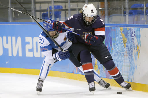 Tea Villila of Finland and Lyndsey Fry of the Untied States battle for control of the puck behind the net during the third period of the women's ice hockey game at the Shayba Arena during the 2014 Winter Olympics, Saturday, Feb. 8, 2014, in Sochi, Russia. (AP Photo/Matt Slocum)