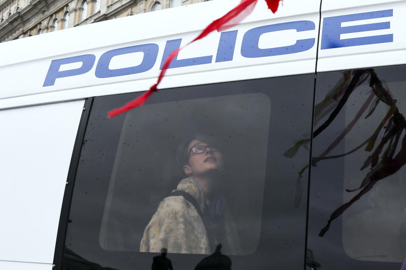 A climate activist is see through a window of a police van during an Extinction Rebellion protest in London, Oct. 7, 2019. (Photo: Alberto Pezzali/AP)