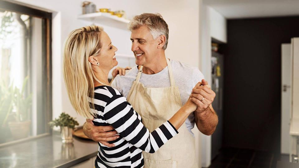 happy mature couple keeping each other company in the kitchen.