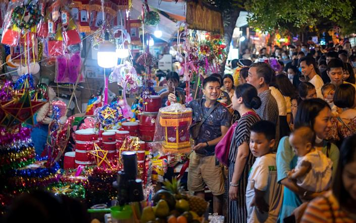 People shop for Mid-Autumn Festival goods on Hang Ma Street in which houses and sidewalks turned into makeshift shops amid the pandemic in Hanoi - Getty