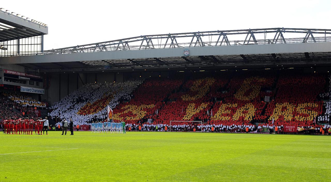 Liverpool fans in the Kop end hold aloft cards to make a mosaic commemorating the 25th anniversary of the Hillsborough disaster, before the English Premier League soccer match between Liverpool and Manchester City at Anfield in Liverpool, England, Sunday April. 13, 2014. (AP Photo/Clint Hughes)