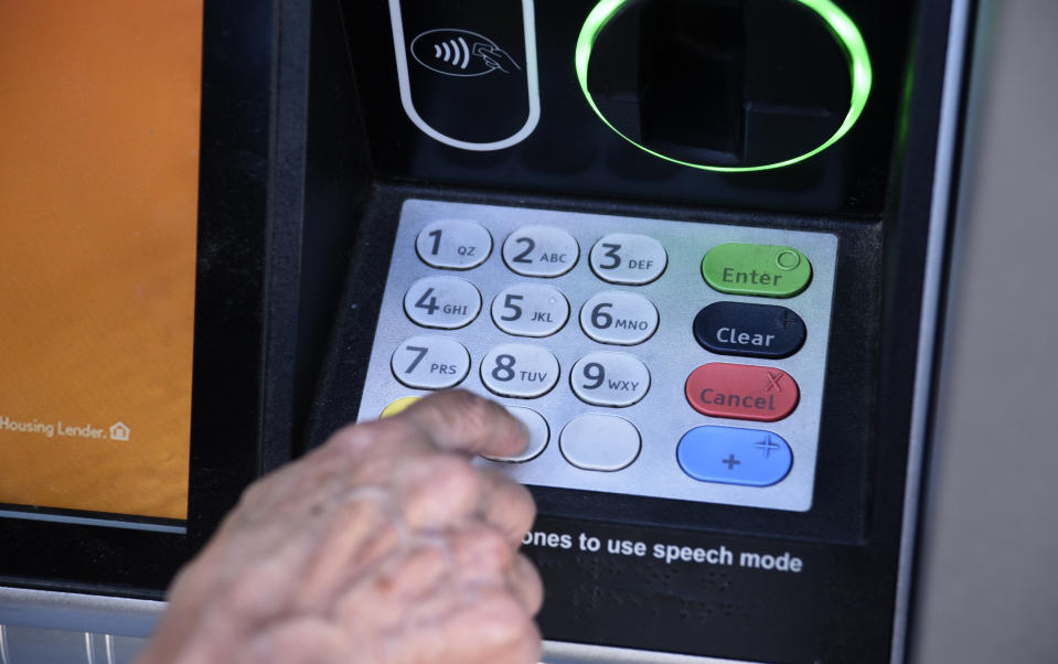 ASHLAND, OREGON - JUNE 17, 2019: A banking customer uses an ATM machine in Ashland, Oregon. (Photo by Robert Alexander/Getty Images)