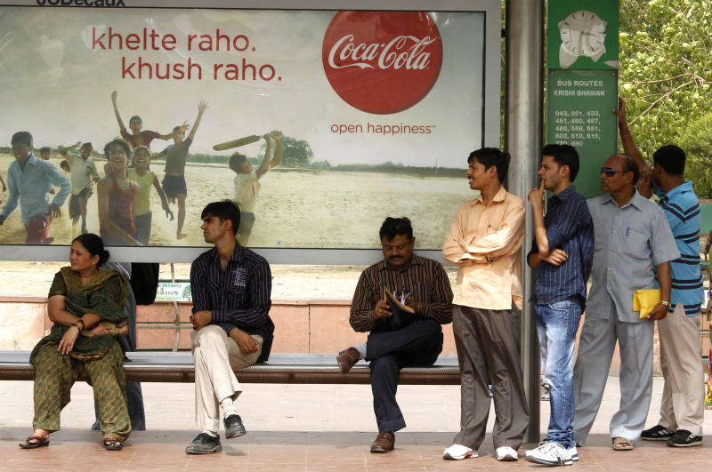 People wait at a bus stop in front of a Coca Cola ad in New Delhi, India, Tuesday, June 26, 2012. The world's biggest beverage maker plans to invest US$5 billion in India from 2012 to 2020. (AP Photo/Manish Swarup)