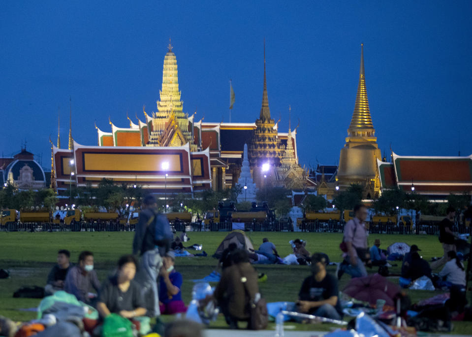 Pro-democracy protesters are seen during dawn at the Sanam Luang field during a protest in Bangkok, Thailand, Sunday, Sept. 20, 2020. Thousands of demonstrators turned out Saturday for a rally to support the student-led protest movement's demands for new elections and reform of the monarchy. (AP Photo/Sakchai Lalit)