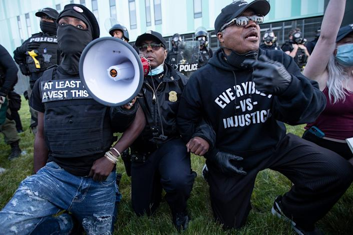 Detroit Police Deputy Chief Todd Bettison, center, takes a knee along with Rev. W.J. Rideout III, right, and protesters in front of the Detroit Police headquarters in Detroit, May 31, 2020.