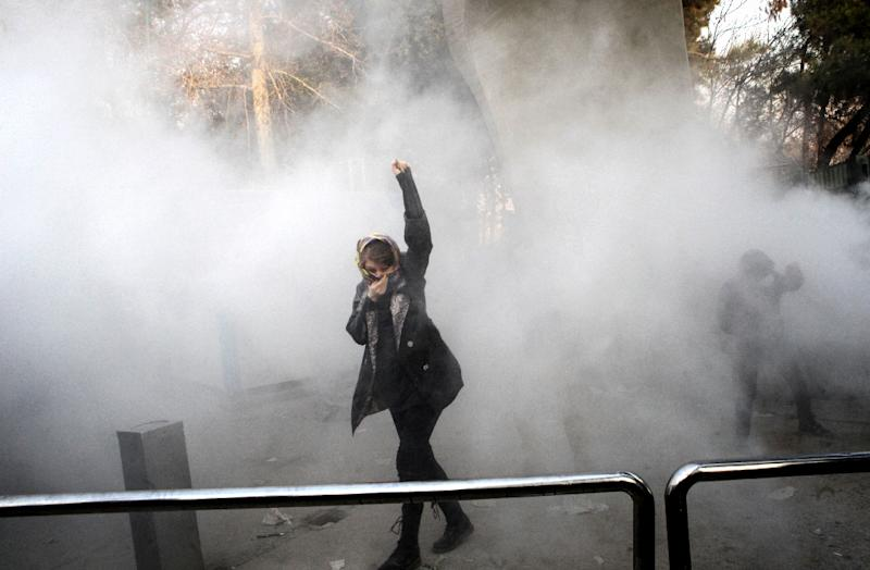 An Iranian woman raises her fist in a cloud of tear gas during a protest at the University of Tehran on December 30, 2017 (AFP Photo/STR)