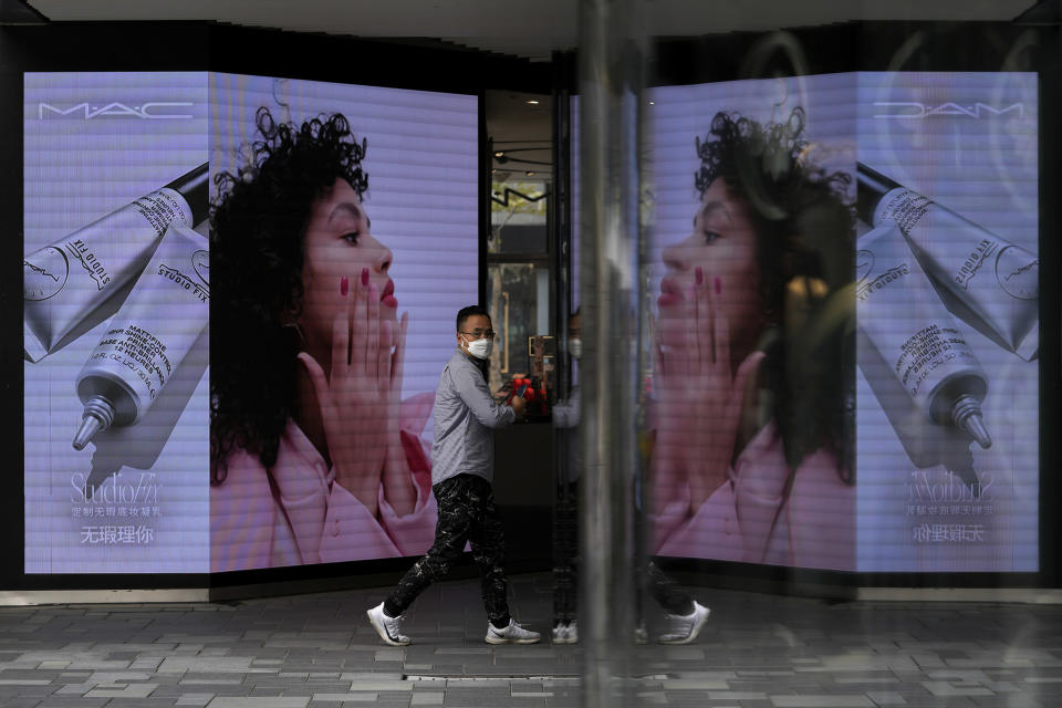A man wearing a face mask to help protect from the coronavirus walks by a cosmetic shop at a capital popular shopping mall in Beijing, Tuesday, Sept. 28, 2021. The World Bank on Tuesday cut its economic growth forecast for developing countries in East Asia due to the impact of the coronavirus's delta variant and called on governments to help the poor and small businesses avoid long-term damage. (AP Photo/Andy Wong)