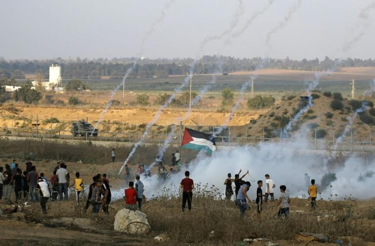 Palestinian protesters flee from tear gas fired by Israeli forces across the fence during clashes along the border in the central Gaza Strip