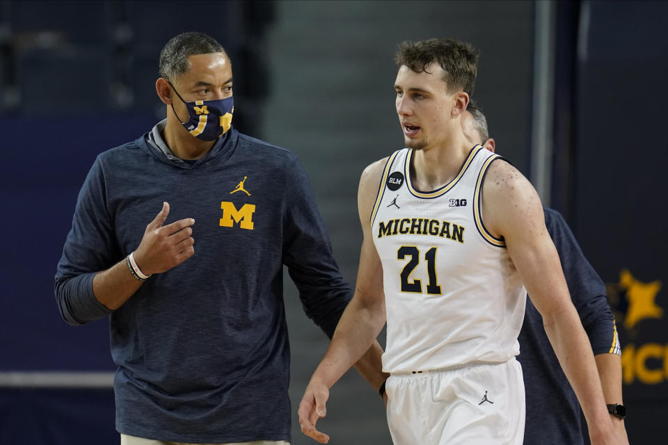 Michigan head coach Juwan Howard talks with Franz Wagner (21) in the second half of an NCAA college basketball game against Ball State in Ann Arbor, Mich., Wednesday, Dec. 2, 2020. (AP Photo/Paul Sancya)