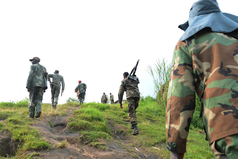M23 rebel group fighters walk on June 3, 2013 in Mutaho toward the frontline to fight troops from the Democratic Republic of Congo Armed Forces