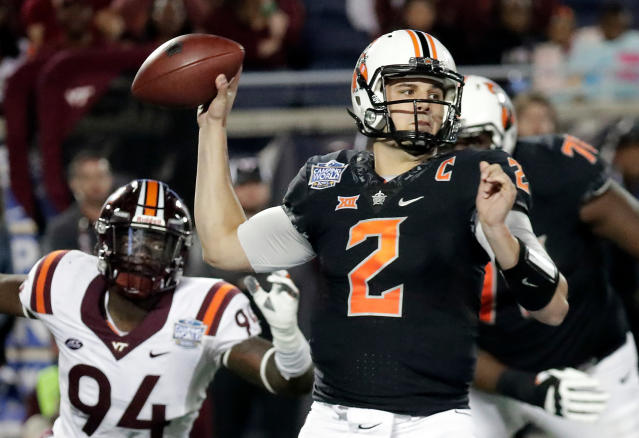 FILE - In this Dec. 28, 2017, Oklahoma State quarterback Mason Rudolph (2) throws a pass as Virginia Tech defensive end Trevon Hill (94) closes in during the second half of the Camping World Bowl NCAA college football game in Orlando, Fla. Every quarterback prospect in the upcoming NFL draft has a major flaw or drawback that keeps them from being the consensus best one of the bunch. (AP Photo/John Raoux, File)