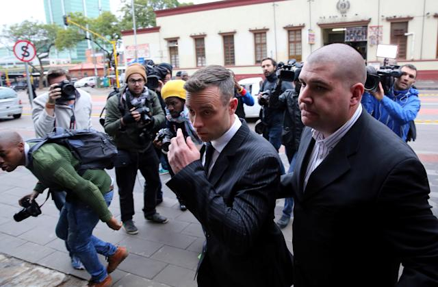 Former Paralympian Oscar Pistorius (C) is followed by members of the media as he leaves during a court break at the Pretoria High Court, South Africa June 13,2016. REUTERS/Siphiwe Sibeko