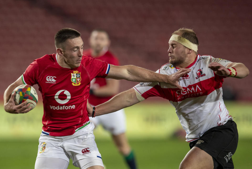 British and Irish Lions' Josh Adams, left, is challenged by South African Lions' PJ Botha during a warm-up rugby match between South Africa Lions and British and Irish Lions at Ellis Park stadium in Johannesburg, South Africa, Saturday, July 3, 2021. (AP Photo/Themba Hadebe)