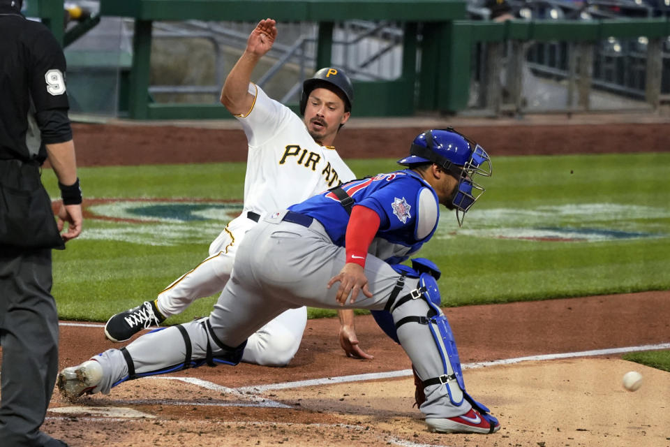 Pittsburgh Pirates' Bryan Reynolds slides as Chicago Cubs catcher Willson Contreras waits for the relay throw during the second inning of a baseball game in Pittsburgh, Saturday, April 10, 2021. Reynolds scored from second on a single by Colin Moran. (AP Photo/Gene J. Puskar)