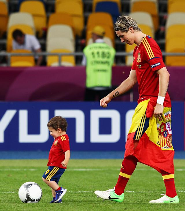 KIEV, UKRAINE - JULY 01: Fernando Torres of Spain watches his son Leo Torres kick a ball on the pitch following victory in the UEFA EURO 2012 final match between Spain and Italy at the Olympic Stadium on July 1, 2012 in Kiev, Ukraine. (Photo by Alex Grimm/Getty Images)