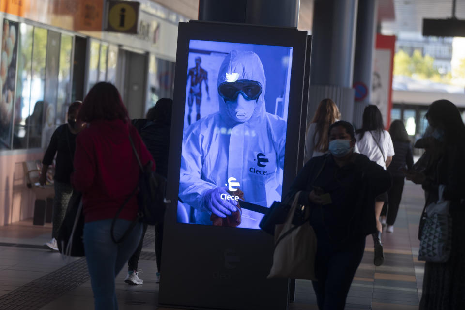 People pass by a poster thanking medical workers at a bus station in Madrid, Spain, Wednesday, Oct. 7, 2020. Spain has become the first western Europe to accumulate more than 1 million confirmed infections as the country of 47 million inhabitants struggles to contain a resurgence of the coronavirus. (AP Photo/Paul White)