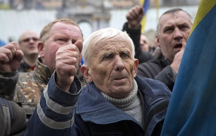 Men shout slogans during mourning for protesters killed in recent clashes, in central Kiev, Ukraine, Saturday, Feb. 22, 2014. Protesters in the Ukrainian capital claimed full control of the city Saturday following the signing of a Western-brokered peace deal aimed at ending the nation's three-month political crisis. The nation's embattled president, Viktor Yanukovych, reportedly had fled the capital for his support base in Ukraine's Russia-leaning east. (AP Photo/Darko Bandic)