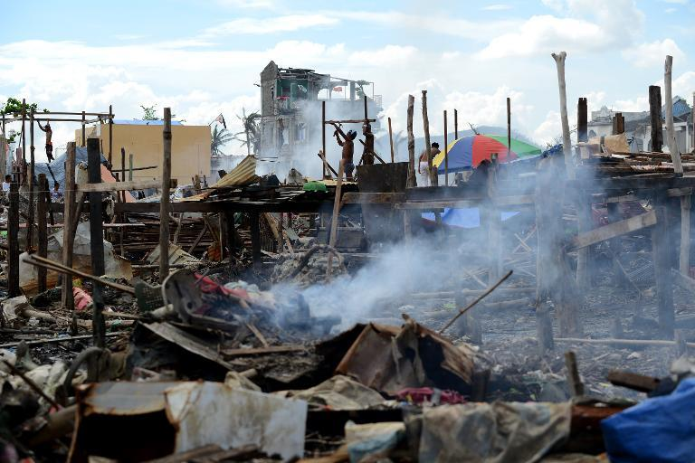 Typhoon survivors build a makeshift house among debris of destroyed houses in Tacloban, Leyte province on December 7, 2013